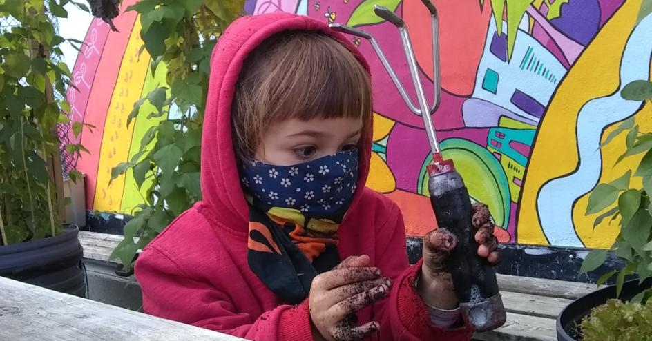 Une fillette masquée regarde avec attention son rateau avec les mains couvertes de terre