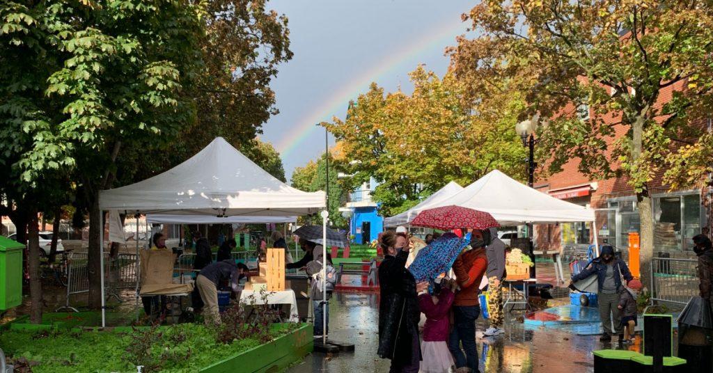 Un arc-en-ciel brille au dessus du marché fermier du roulant comptant quelques tentes blanches. Des personnes à l'avant-plan ont des parapluies.